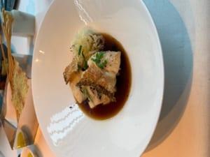 コンソメスープに表面がカリカリに焦げた真鯛